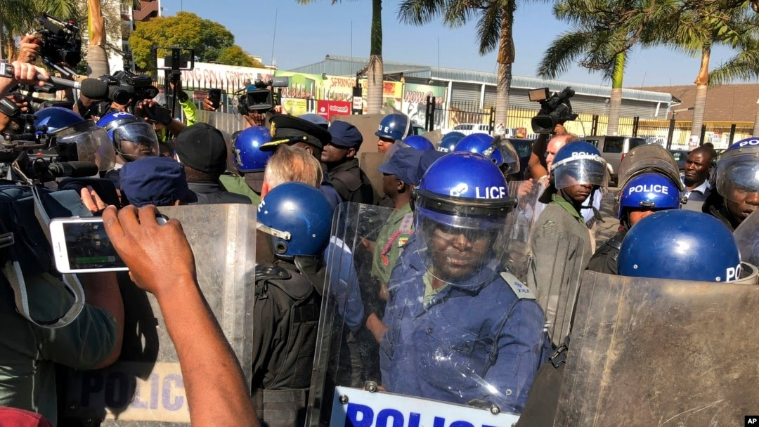 Riot police break up a press conference by opposition leader Nelson Chamisa in Harare, Zimbabwe, Aug. 3, 2018.