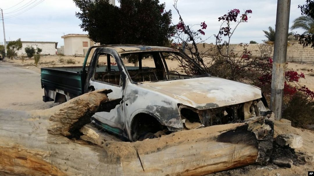 FILE - A burned truck is seen outside Al-Rawda Mosque in Bir al-Abd northern Sinai, Egypt a day after attackers killed hundreds of worshippers, on Nov. 25, 2017.