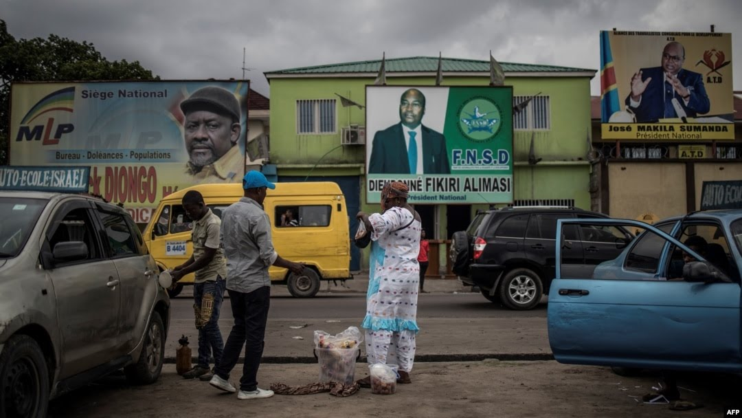 A woman sells beverages in front of electoral posters in Kinshasa, Democratic Republic of the Congo, Dec. 17, 2018.